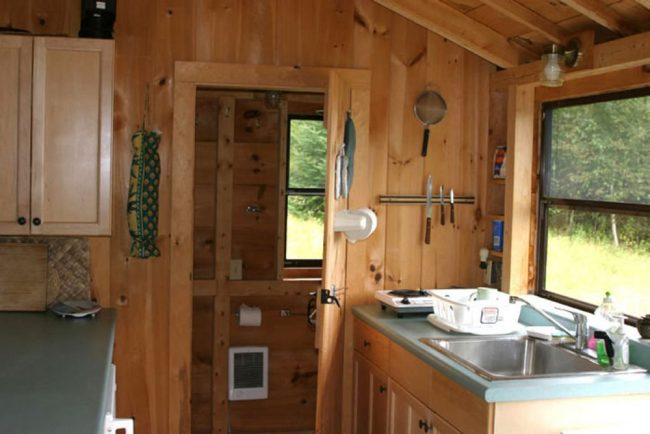 Log Cabin Kitchen features, stove, microwave, toast oven, compact refrigerator.